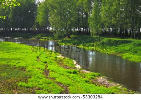 meadow on riverbank - stock photo