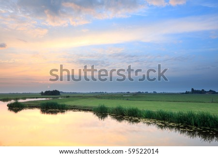 Meadow with canal at sunrise, the Netherlands - stock photo