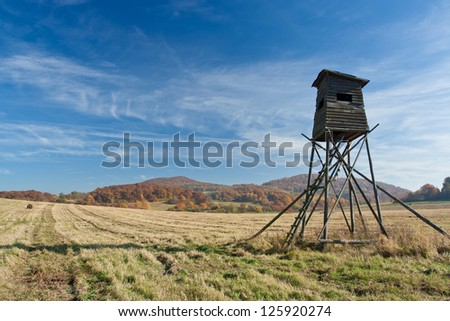 Meadow with deer-stand   with blue sky - stock photo