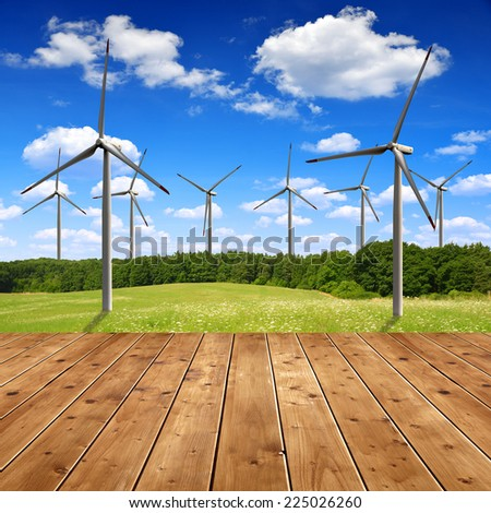 Meadow with wind turbines and wooden planks - stock photo