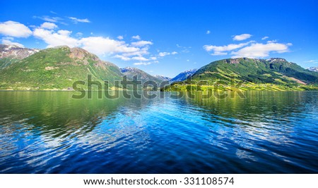 Meadows and village on Hardanger Fiord. Norway shore with view. Hardanger Fiord. Norway. - stock photo