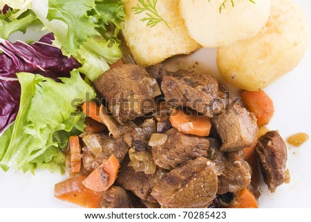 Meal of stewed beef steak with roast potatoes and fresh salad