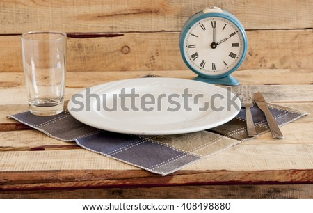 Meal time table place setting with alarm clock - stock photo