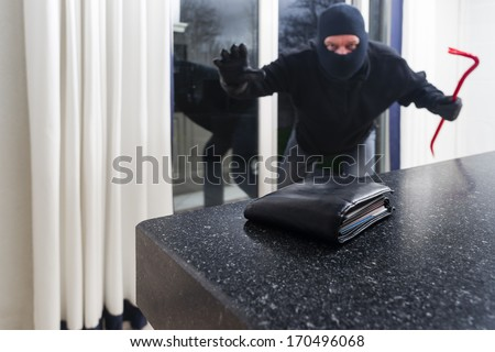 Mean looking burglar enters a kitchen to grab a wallet from the kitchen counter