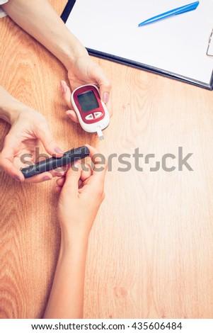 Measure child glucose level blood test diabetes little boy using glucometer - stock photo