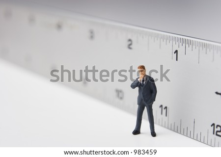 Measure of a man, business figure standing in front of a ruler