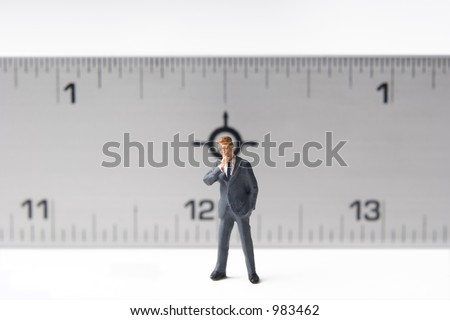Measure of a man, business figure standing in front of a ruler - stock photo