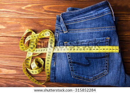 Measure tape roll on a back pocket of blue denim on a wooden background - stock photo