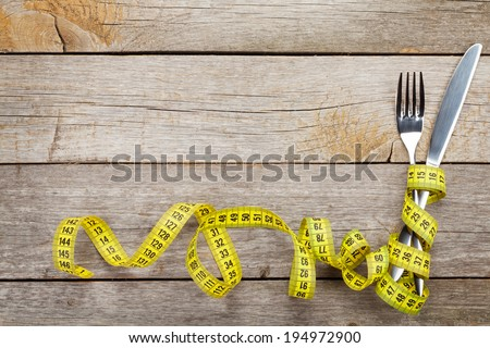 Measure tape with knife and fork. Diet food on wooden table with copy space - stock photo