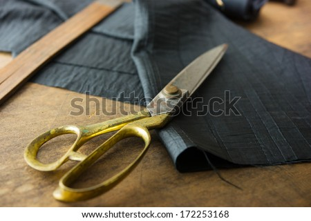 Measuring and cutting textile or fine cloth. Work table of a tailor. Gold scissors and black fabric. - stock photo