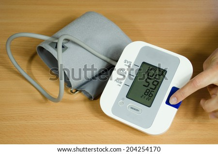 measuring blood pressure and female finger presses the start button