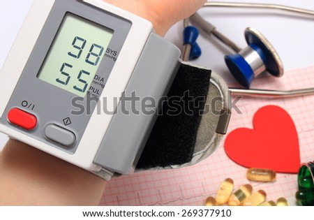 Measuring blood pressure, heart shape, stethoscope and tablets on electrocardiogram, medicine concept - stock photo