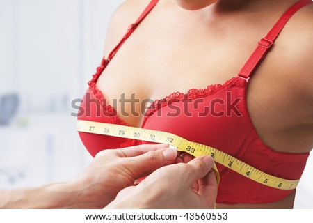 Measuring bust size of woman wearing red bra