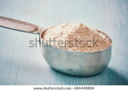Measuring cup spoon with flour on blue wooden table