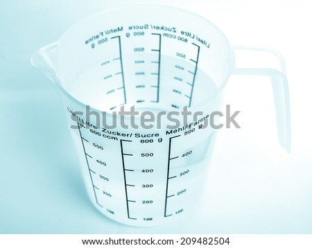 Measuring cup with metric scales for water, sugar and flour - cool cyanotype - stock photo