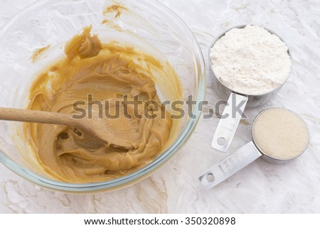 Measuring cups of flour and sugar with a peanut butter mixture in a glass bowl - stock photo