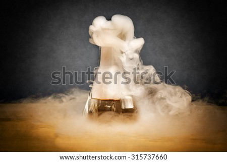 Measuring glass with smoke on a table of a chemical laboratory - stock photo
