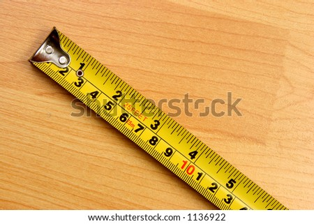 Measuring scale in centimeters and inches over a wooden floor - stock photo