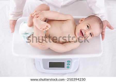 Measuring smiling beautiful comfortable little baby child - stock photo