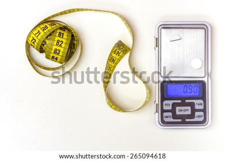 Measuring Tape and a Medicine Scale on a white background - stock photo