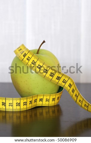 Measuring tape and apple on the table