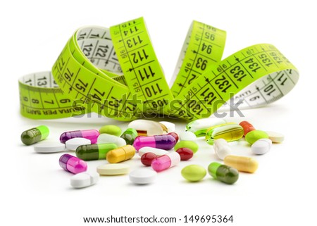 measuring tape and medicines on white background - stock photo