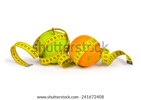 Measuring tape around the orange and green apple. Concept slim figure - stock photo