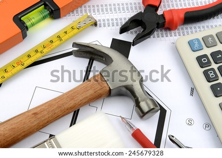 measuring tape, hammer, pliers, gloves and water level on plans - stock photo