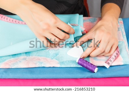 measuring tape in the hands of a seamstress at work.  - stock photo