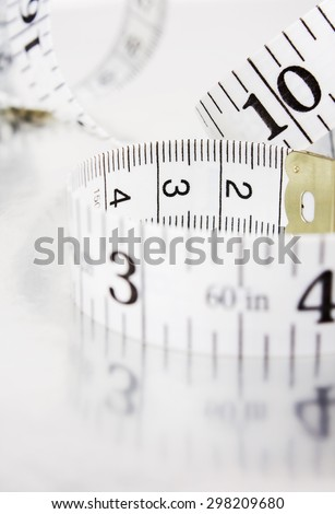 Measuring tape on a gray background with reflection