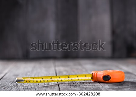 Measuring tape on a wooden board with copyspace - stock photo