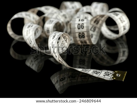 Measuring tape on black background