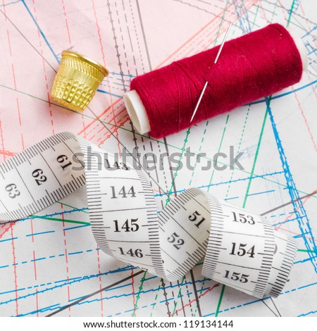 measuring tape, thimble and bobbin of thread - lie of paper patterns of clothing (sewing template plan)