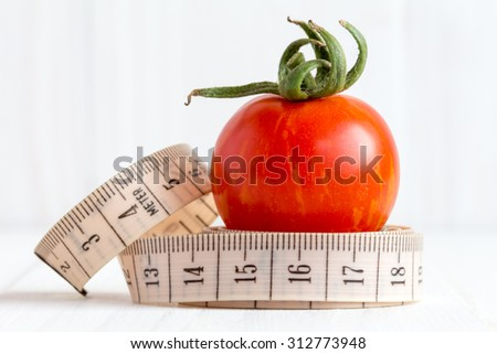 Measuring tape with a small red tomato fruit - stock photo