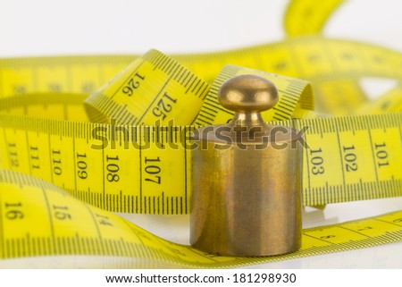 Measuring tape with brass weight in detail - stock photo