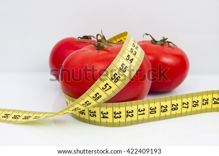 Measuring tape with tomato isolated on white background.