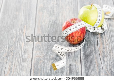 Measuring tape wrapped around a apples. Symbol of diet.