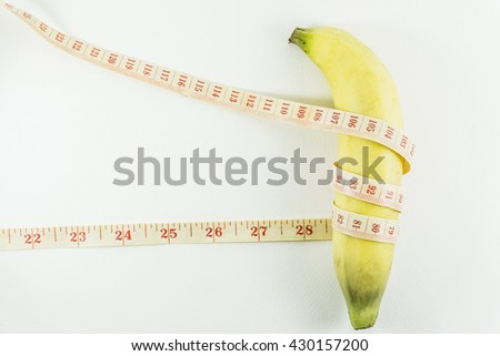 Measuring tape wrapped around a banana. Concept of diet. - stock photo