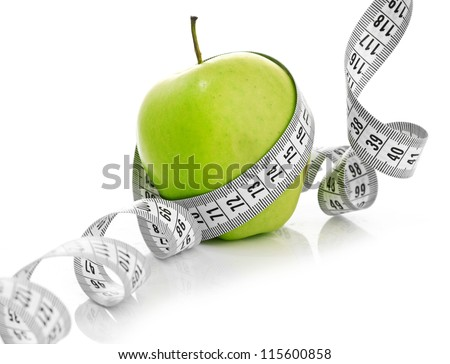 Measuring tape wrapped around a green apple as a symbol of diet. - stock photo