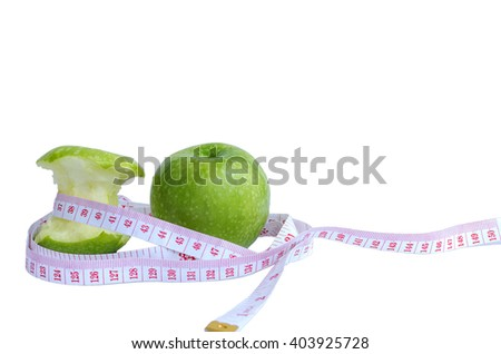Measuring tape wrapped around a green apple at a symbol of diet.