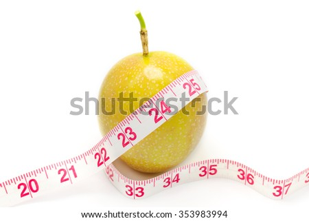 Measuring tape wrapped around a passion fruit as a symbol of diet. - stock photo