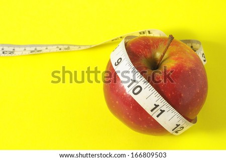 Measuring Tape Wrapped Around a Red Apple as Symbol of Diet