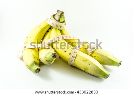 Measuring tape wrapped around bananas. Concept of diet. - stock photo