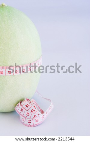 Measuring tapes around a melon against a light blue background. Shallow D.O.F. - stock photo