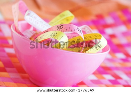 Measuring tapes in a pink bowl on a placemat. Shallow D.O.F. - stock photo