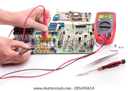 Measuring the electronic components on the motherboard of the computer. On white. - stock photo
