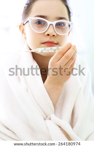 Measuring the temperature of a sick child. Girl wrapped in a blanket, the thermometer  - stock photo