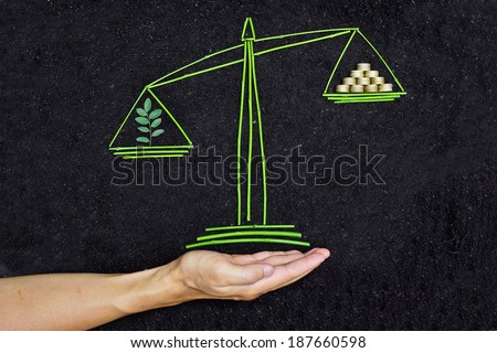 Measuring tree and golden coins on a balance scale - stock photo