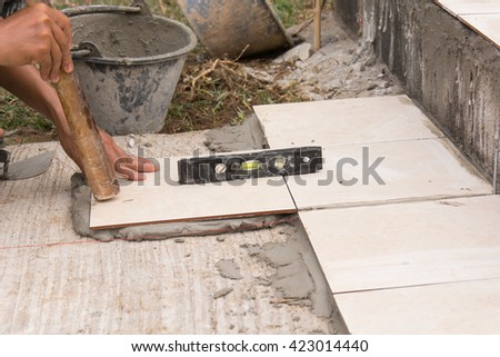 measuring vertical linearity of installation ceramic tiles during renovation - stock photo