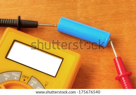 Measuring with digital multimeter of rechargeable battery - stock photo